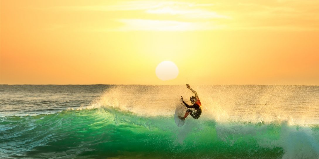 Surfer Surfing at Sunrise with the sun in the background