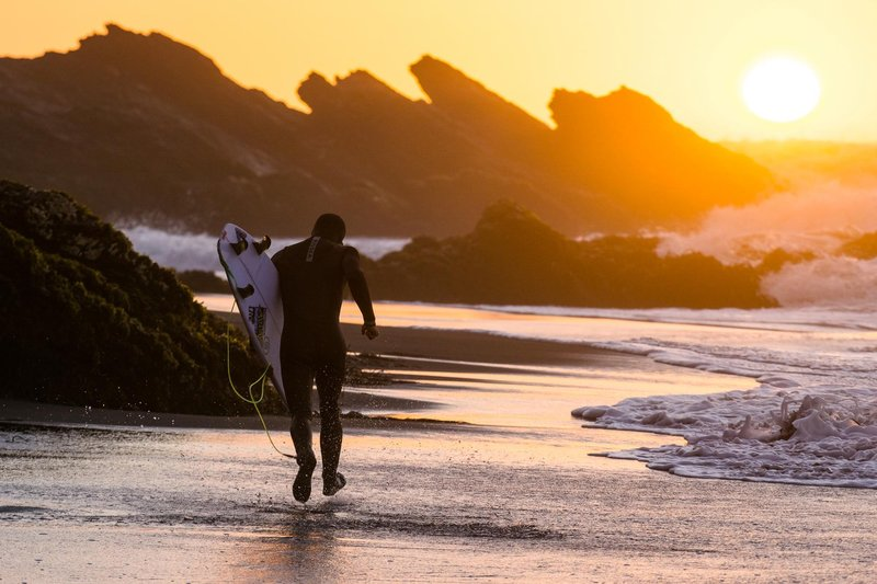 surfer-cam-richards-heads-out-for-one-more-wave-at-sunset-on-a-beach-surf-en-chile