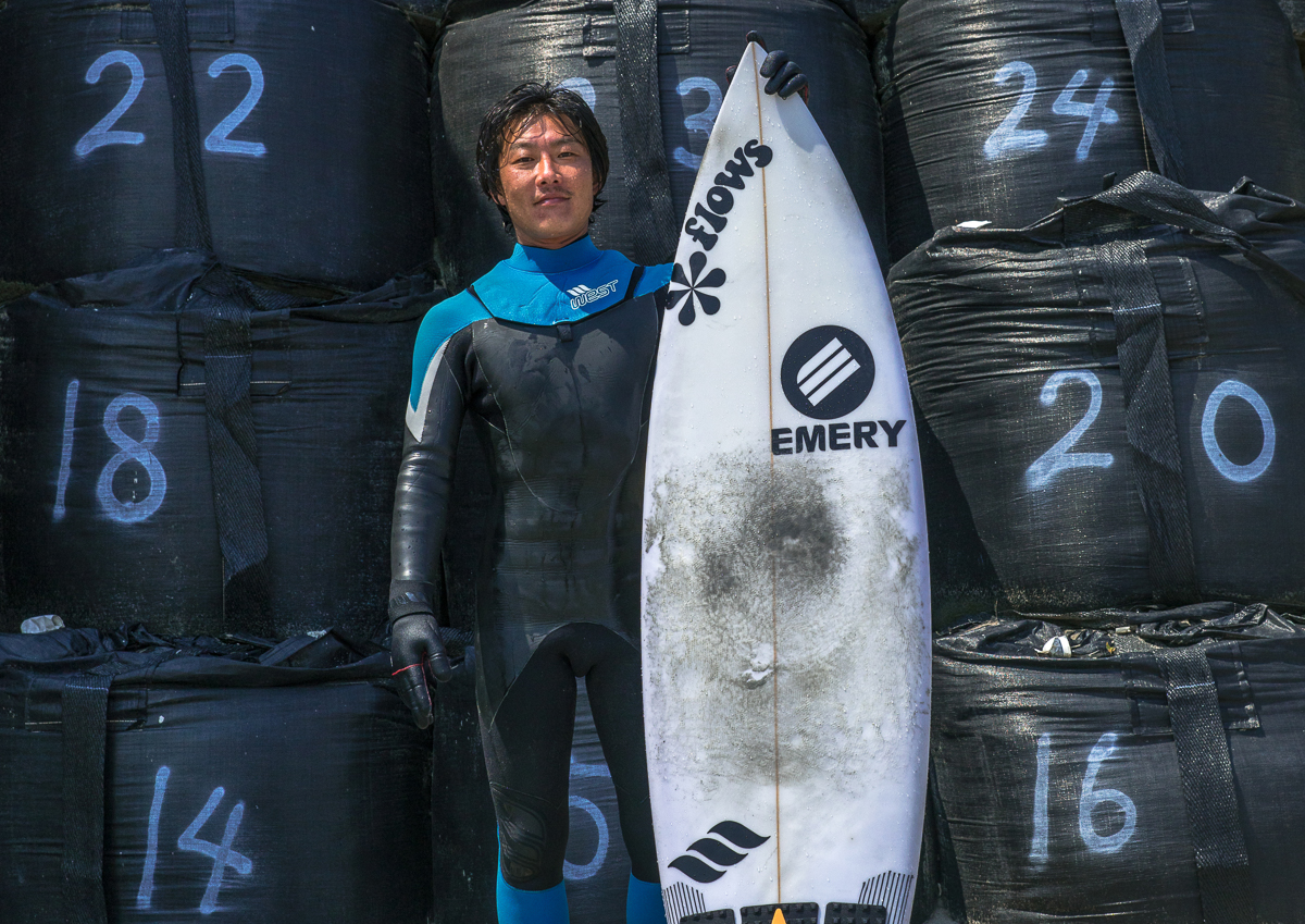 Japanese surfer in front of bags with contaminated sand after the daiichi nuclear power plant irradiation, Fukushima prefecture, Tairatoyoma beach, Japan