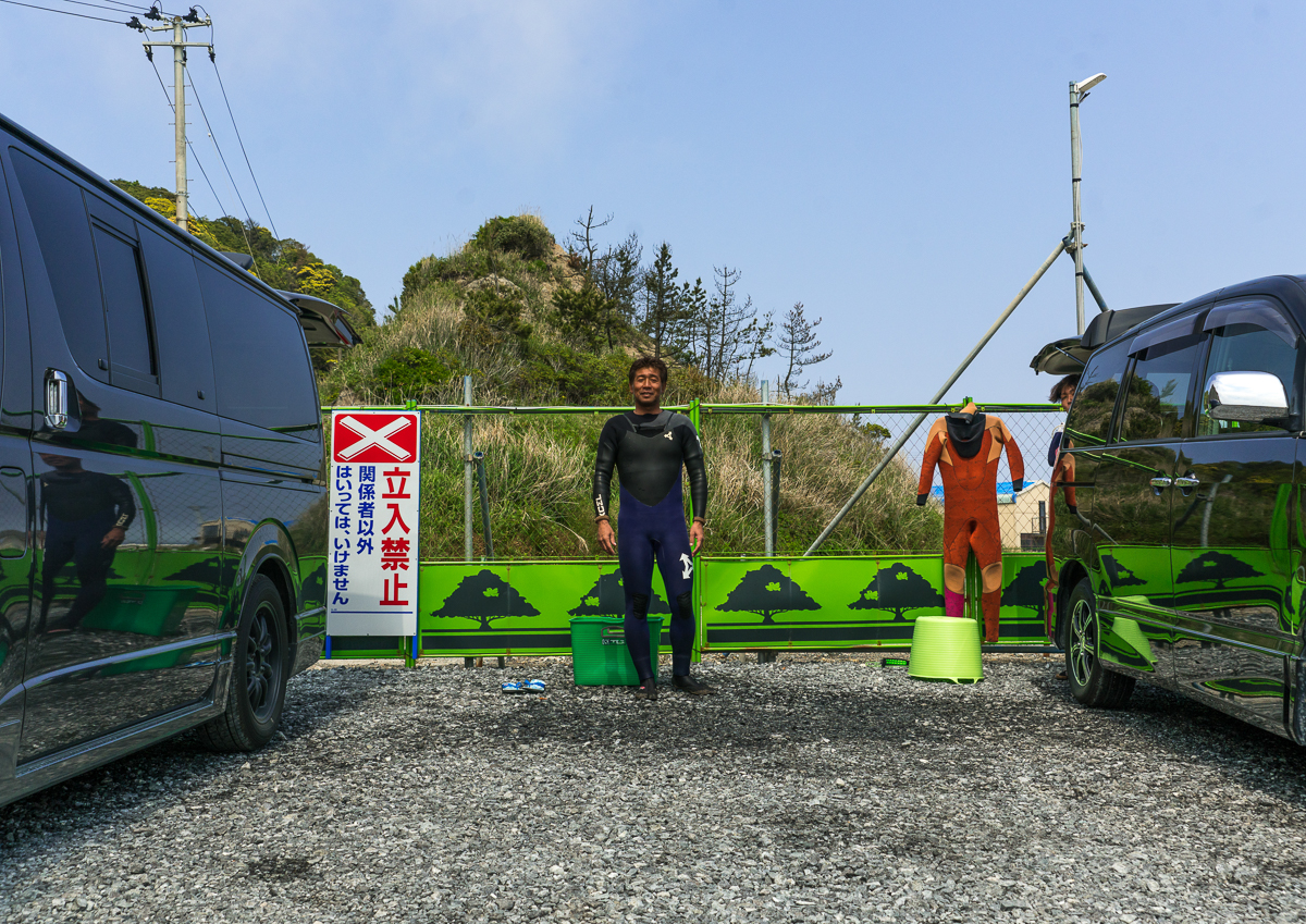 Japanese surfer in the contaminated area in front of a authorized entry prohibited sign, Fukushima prefecture, Tairatoyoma beach, Japan
